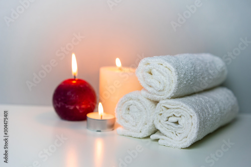 SPA and wellness photo with stack of white towels and candles light, horizontal orientation.