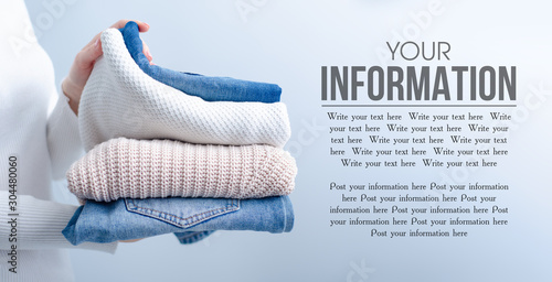Fotografía  Stack of knitted clothes and jeans in female hands on grey blurred background, s