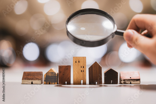 Photo Hand holding magnifying glass and looking at house model, house selection, real estate concept