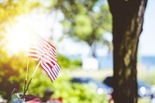 Closeup Shot Of Small Untied Statues Flag Attached To A Car With A Blurred Background