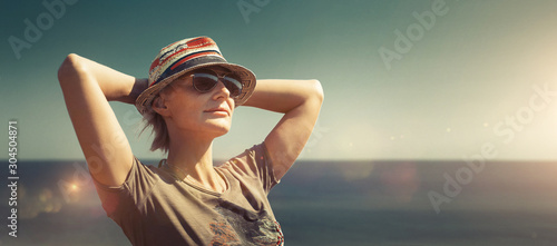Foto auf Leinwand Khaki Concept of freedom, happiness, tourism, adventure and leisure. Attractive middle-aged woman in hat, keep your hands to your head and enjoy picturesque landscape at resort in sunny light