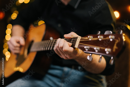 Obraz Guy plays guitar close-up. Against the background of a decorated Christmas tree with a garland - fototapety do salonu