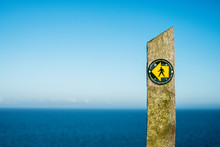 Close Up Of Stone Signpost With Ocean In Background
