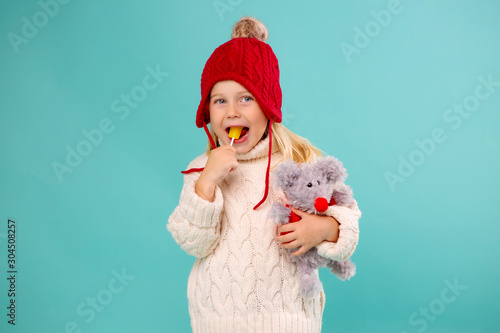 Obraz little blonde girl in a red knitted hat and sweater holding a soft toy mouse and a yellow Lollipop. isolate on blue background, space for text - fototapety do salonu