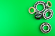 canvas print picture - Ball bearing lying on a green background with copy space on the left side. Flat view from above.