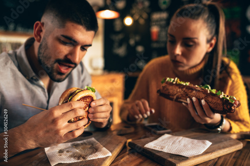 friends eating unhealthy food burgers and sausages Wallpaper Mural