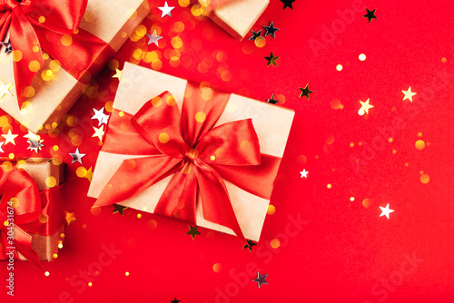 Fototapeta Several gift boxes with bows on a red background. obraz