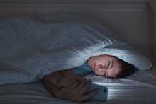 Sleepy Depressed Teenager Surfing In The Internet On His Mobile Phone Lying On Bed In The Dark. Web Addiction, Smartphone Dependency, Internet Trap. Insomnia, Nomophobia, Sleep Disorder Concept.