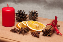 Christmas Composition – Candle, Dried Orange, Anise, Cinnamon. On Wooden Background