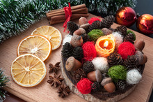 Christmas Composition - Lit Candle Wax, Cones, Acorns, Balls, Dried Orange, Anise, Cinnamon. On Wooden Background.