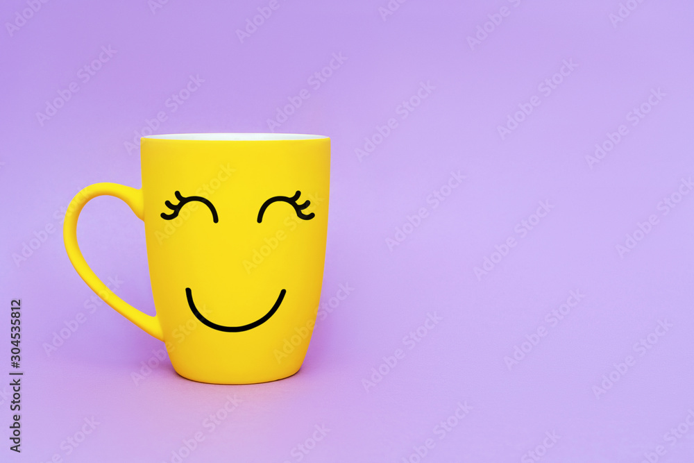 Smiley yellow coffee cup on purple background. Happy friday word concept. Minimalism style, romantic mood, good morning, happiness, break time
