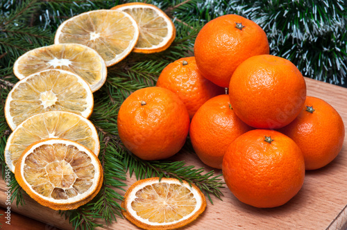 Christmas composition – orange, fir tree branch. On wooden background.