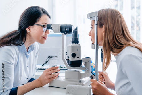 Fotografía  Adult female doctor ophthalmologist checking eye vision of young girl in modern