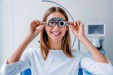 Young Woman Checking Vision With Eye Test Glasses During A Medical Examination At The Ophthalmological Office