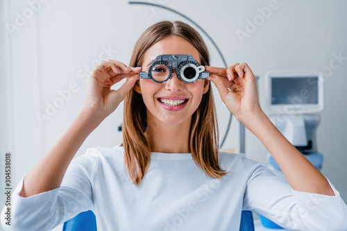Fotomural Young woman checking vision with eye test glasses during a medical examination a