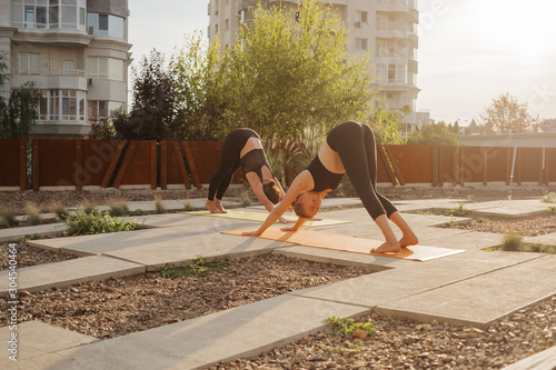 Fototapeta Two young girls practicing stretching and yoga workout exercise together obraz