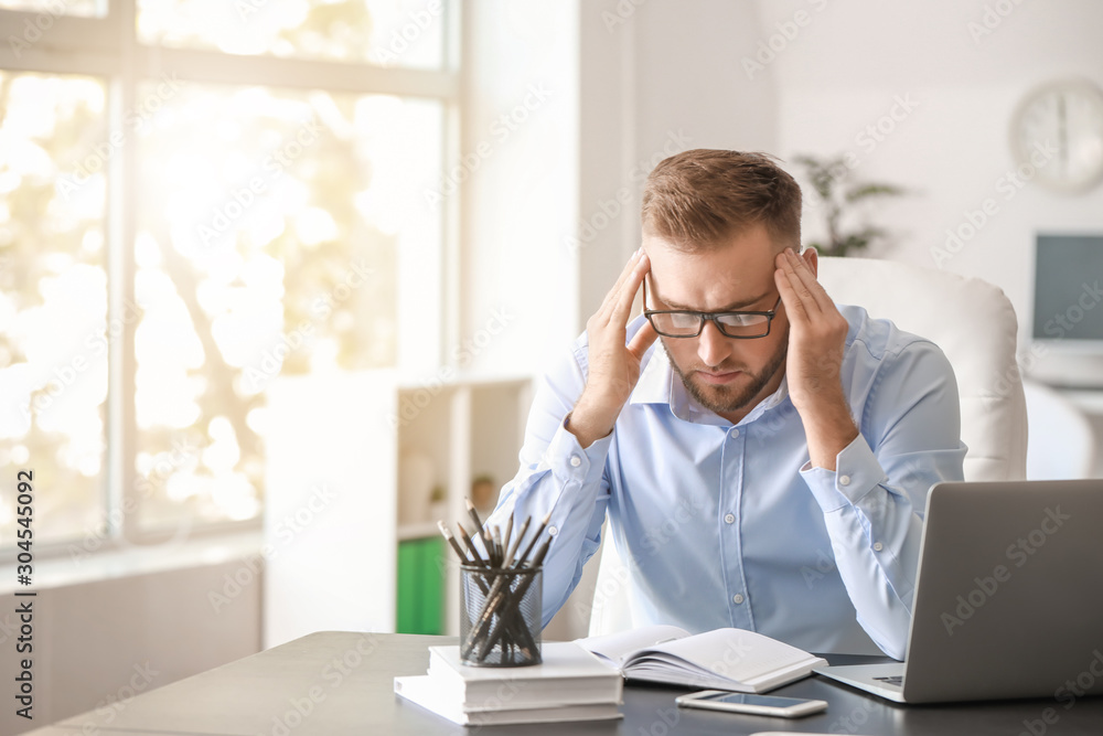 Fototapeta Young man suffering from headache in office