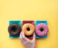 Female Hand Takes A Donut With A Plate On A Yellow And Background. Trendy Donut Assorted. The Apartment Was Lying. Donut Delivery Concept.