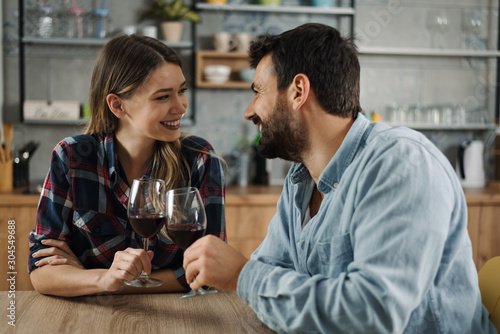 Cuadros en Lienzo  Young couple in love enjoying in conversation while drinking red wine