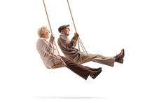 Elderly Man And Woman Swinging On A Wooden Swings