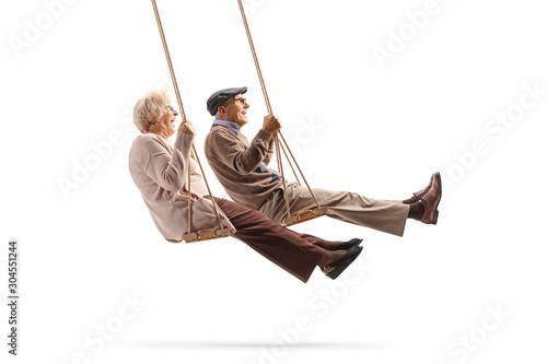 Carta da parati Elderly man and woman swinging on a wooden swings