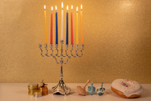 Day 7 Of Jewish Religious Holiday Hanukkah With Traditional Chandelier Menorah, Spinning Top Toys (dreidels) And A Doughnut And Chocolate Coins On White Wooden Table And Golden Glittering Background