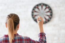 Young Woman Playing Darts Indo...