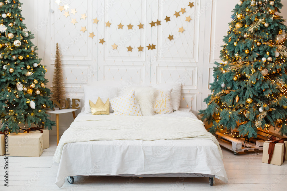 Fototapety, obrazy: Romantic bedroom in light colors with a lot of garland lights decorated for New Year Celebrating. Christmas mood at home. White bedroom and Christmas spruces. Romantic interior. Breakfast in a bed
