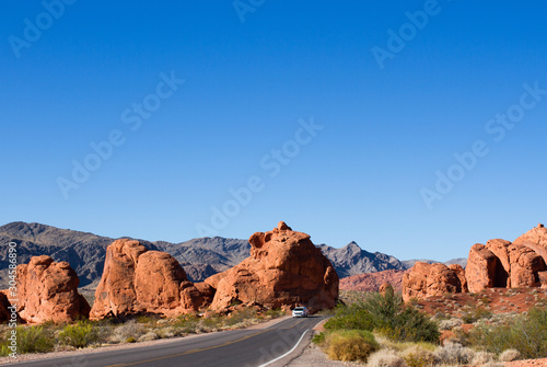 Car on scenic drive through the Seven Sisters rock formation at Valley of Fire Wallpaper Mural