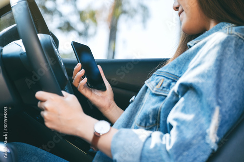 Closeup image of a woman using mobile phone while driving a car