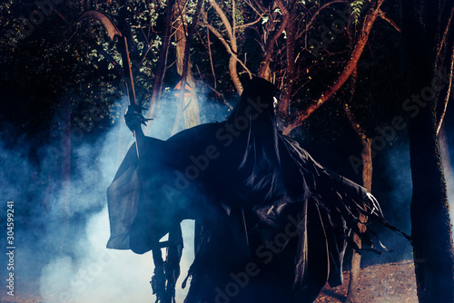 Grim Reaper standing in the fog at night with his scythe. Wallpaper Mural
