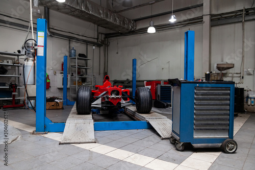 Fotografía  The process of repairing and restoring a red sports car at a pitstop in the service station or a repair workshop on a lift