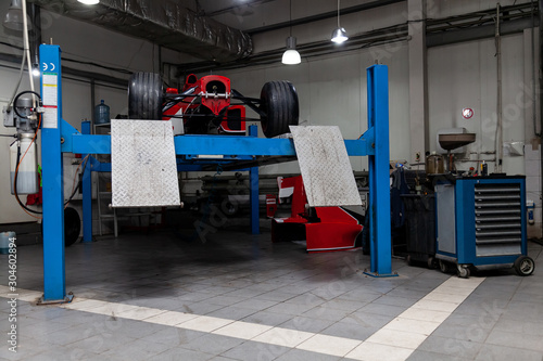 The process of repairing and restoring a red sports car at a pitstop in the service station or a repair workshop on a lift Canvas Print