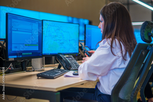 Fotografie, Tablou Female security guard sitting and monitoring modern CCTV cameras in a surveillance room