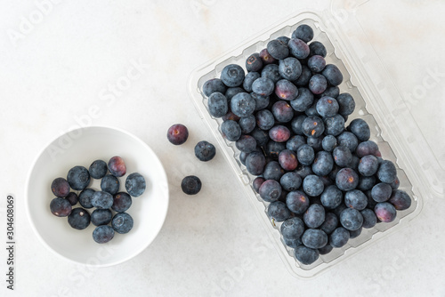 Fotografering Open clamshell container of blueberries on a white granite counter, small white