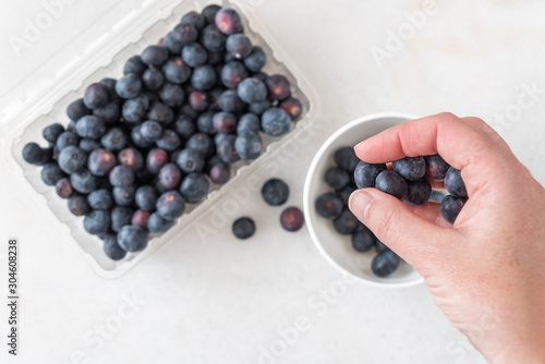 Fényképezés Woman's hand picking blueberries from clamshell container on a white granite cou