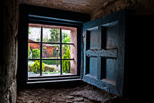 Garden View Through An Old Colonial Style Window With Fence And Shutter