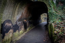 LIVERPOOL, ENGLAND, DECEMBER 27, 2018: Entrance To The Creepy Dark Tunnel To The St James's Cemetery Beside Liverpool Cathedral, With Walls Shaped By Old Moldy Gravestones