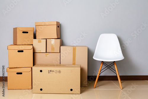 Photo Moving boxes with packed stuff and chair for moving