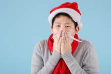 Asian Preteen Boy Wearing Santa Hat And Using Napkin With Blue Background.