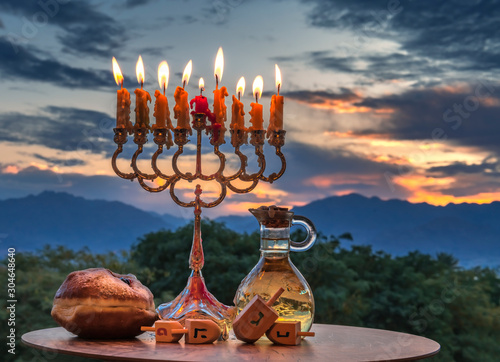 Hanukkah holiday with menorah, burning candles, sweet donut, jar of olive oil an Canvas Print