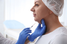 Mature Woman With Double Chin Receiving Injection In Clinic