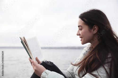 Fotografia, Obraz  Woman reading book near river on cloudy day