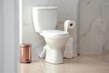 Modern Toilet Bowl With Roll Of Paper In Bathroom
