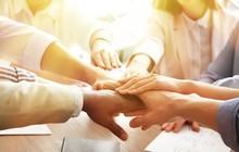 Volunteers Putting Hands Toget...
