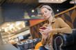 Leinwanddruck Bild - young businesswoman smiling on the phone in a cafeteria