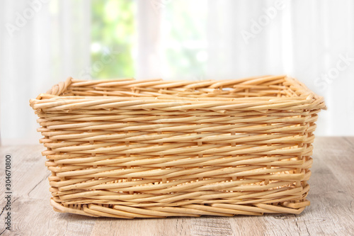 Fototapeta Wicker basket on a wooden table