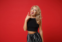 Funny Young Woman Girl In Black Clothes Posing Isolated On Bright Red Wall Background. People Sincere Emotions Lifestyle Concept. Mock Up Copy Space. Showing Tongue, Depicting Heavy Metal Rock Sign.