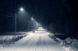 Leinwanddruck Bild - road in the blizzard snow in winter at night. In the light of lamps visible falling snow.