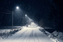 Road In The Blizzard Snow In Winter At Night. In The Light Of Lamps Visible Falling Snow.